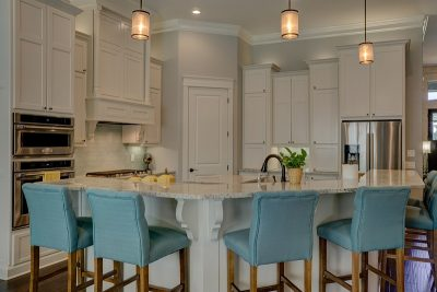 white kitchen with light blue chairs around the island