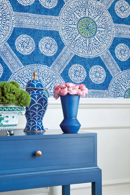blue desk with vases in front of wall with blue medallion wallpaper