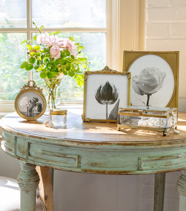 antique side table with framed pictures